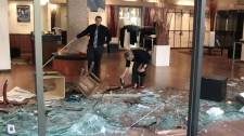 Employees of a menswear store clean up in Vancouver, B.C., on Thursday, June 16, 2011. (Darryl Dyck / THE CANADIAN PRESS)
