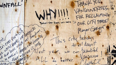 Messages from Vancouver Mayor Gregor Robertson, top right, and British Columbia Premier Christy Clark, bottom right, are written along with others on plywood covering the windows of the damaged Hudson's Bay Company store in Vancouver. (Darryl Dyck / THE CANADIAN PRESS)