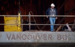 A Seaspan Vancouver Shipyards worker stands on a barge under construction in North Vancouver, B.C. in 2011. (Darryl Dyck / THE CANADIAN PRESS)