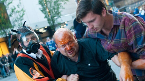 Dean Seski, left, and Chris McLelland carry Robert MacKay away from a mob of rioters after the Stanley Cup riot in Vancouver. June 19, 2011. (CTV)