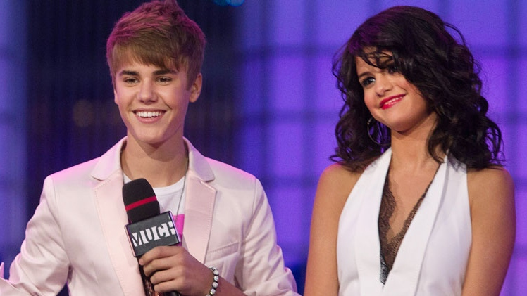 Justin Bieber and girlfriend Selena Gomez stand on stage during the 2011 MuchMusic Video Awards in Toronto on Sunday, June 19, 2011. (Darren Calabrese / THE CANADIAN PRESS)