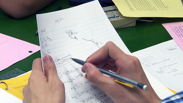 A student works on his math assignment in school in this photo captured from video.