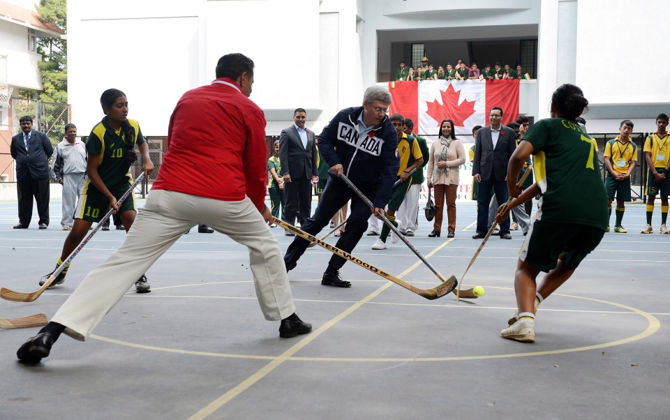 In this November 9, 2012 file photo, Canadian Prime Minister Stephen Harper, centre, and Canadian Minister of State (Sport) Bal Gosal, second left, play ball hockey in Bangalore, India. (THE CANADIAN PRESS/Sean Kilpatrick)