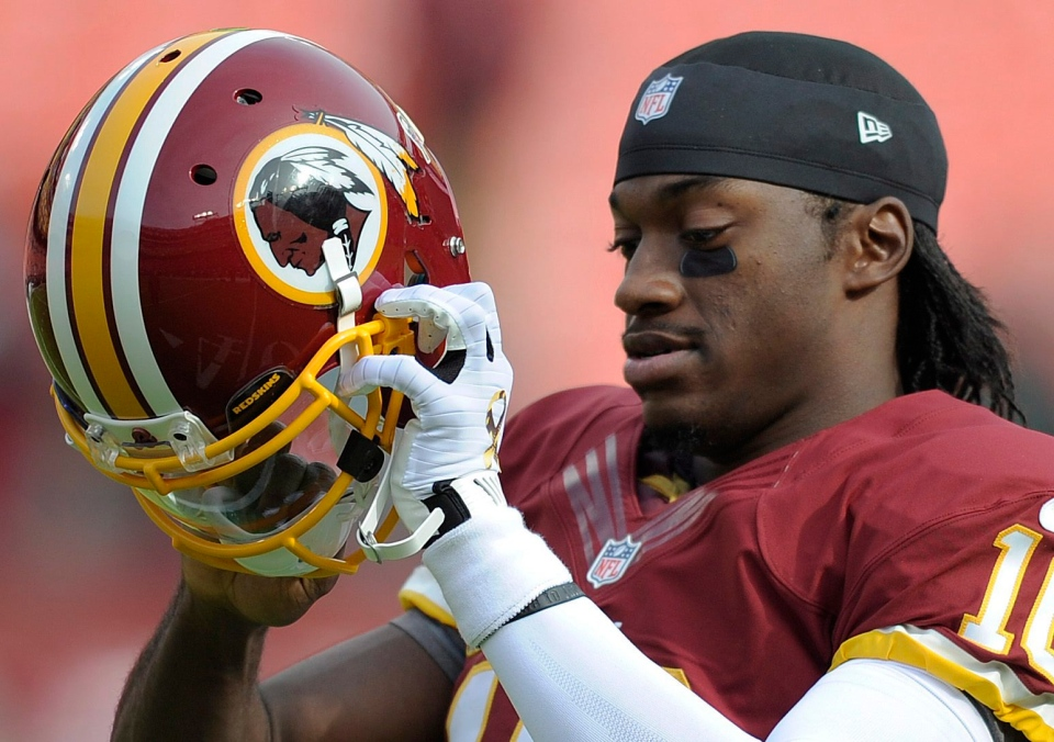 Washington Redskins quarterback Robert Griffin III prepares to put on his helmet before an NFL football game in this November 2012 file photo. (AP / Nick Wass)