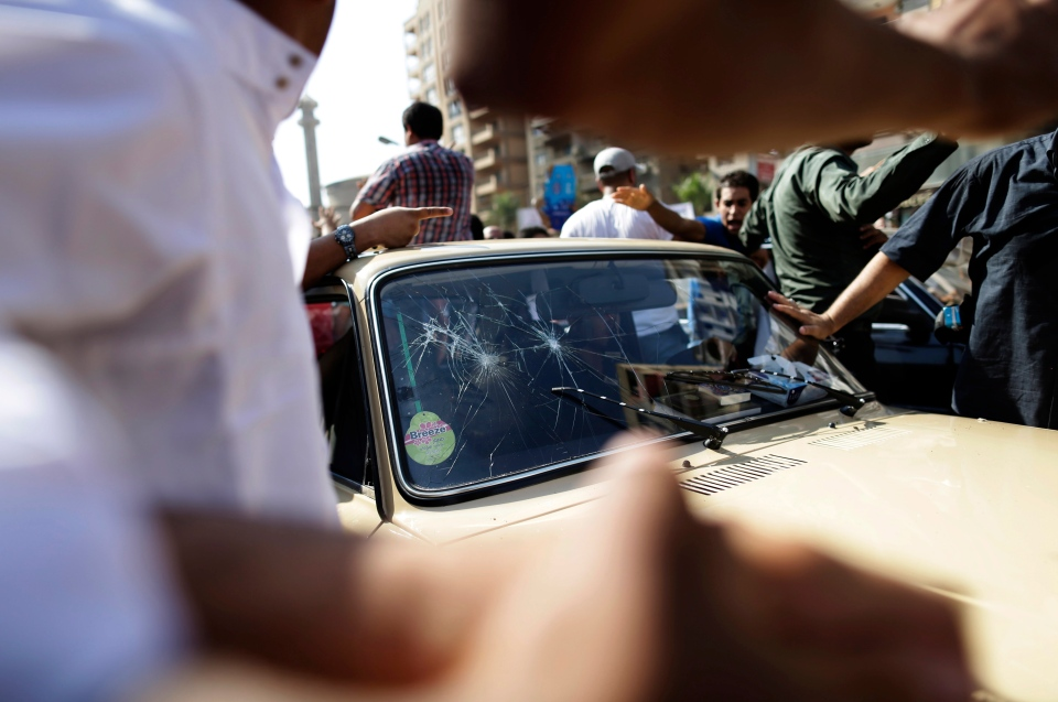 Supporters of Egypt's ousted President Mohammed Morsi surround an army military car and throw stones on it during a protest in Cairo, Egypt in this September 2013 file photo. (AP Photo/Hassan Ammar)