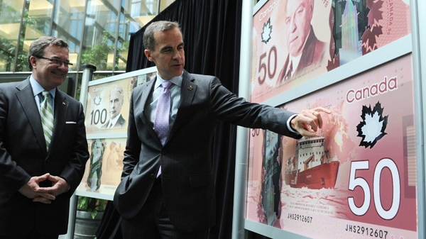 Bank of Canada Governor Mark Carney, right, and Finance Minister Jim Flaherty unveil the new polymer bank notes in $50 and $100 denominations at the Bank of Canada in Ottawa on Monday, June 20, 2011. (Sean Kilpatrick / THE CANADIAN PRESS)