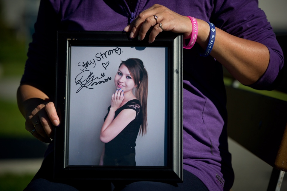 Carol Todd holds a photograph of her late daughter Amanda Todd signed by U.S. singer Demi Lovato with the words 'Stay Strong' in Port Coquitlam, B.C., on Oct. 5, 2013. (Darryl Dyck / THE CANADIAN PRESS)
