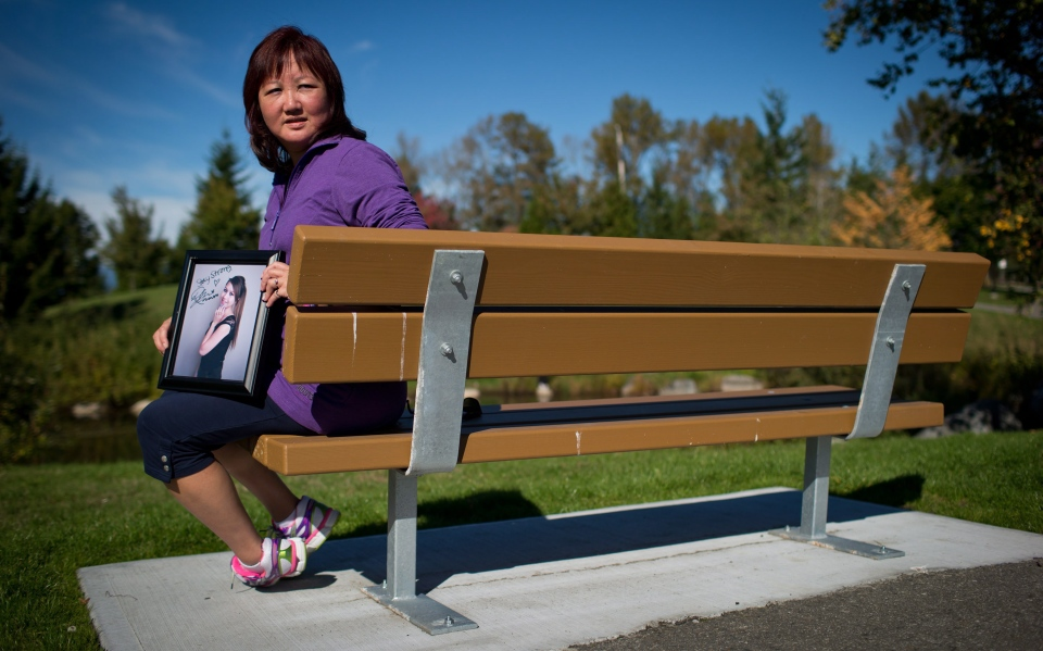 Carol Todd holds a photograph of her late daughter Amanda Todd while sitting on a bench dedicated to her at Settlers Park in Port Coquitlam, B.C., on Sunday October 5, 2013. (Darryl Dyck / THE CANADIAN PRESS)