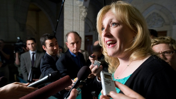 `Labour Minister Lisa Raitt speaks with the media about tabling back to work legislation for the Canada Post lockout following Question Period in the foyer of the House of Commons on Parliament Hill in Ottawa, Monday June 20, 2011. (Adrian Wyld / THE CANADIAN PRESS)