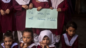 Pakistani school children hold a hand-written sign during a special class to commemorate the anniversary of Malala Yousufzai's shooting by Taliban, at a school in Rawalpindi, Pakistan, Wednesday, Oct. 9, 2013. (AP / Muhammed Muheisen)