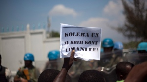 A demonstrator holds up a sign that reads in Creole 'Cholera of UN is a crime against humanity' during a protest against the United Nations peacekeeping mission in Port-au-Prince, Haiti, Friday March 22, 2013. (AP / Dieu Nalio Chery)