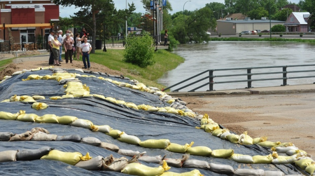 Residents view the flooding in Weyburn, southeast Saskatchewan on Monday, June 20, 2011. (Roy Antal / THE CANADIAN PRESS)