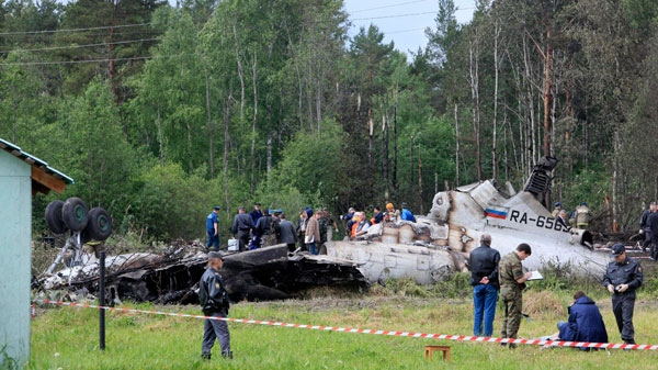 Emergency workers and investigators search a wreckage of Tu-134 plane, belonging to the RusAir airline, near the city of Petrozavodsk Tuesday, June 21, 2011. (AP / Timur Khanov, Komsomolskaya Pravda)