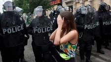 A woman reacts as RCMP officers dressed in riot gear encircle and detain hundreds of people in Toronto on Sunday June 27, 2010. (Chris Young / THE CANADIAN PRESS)