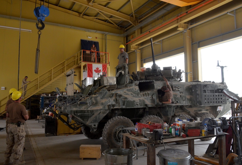 Civilian and military vehicle technicians strip down and clean a Canadian light armoured vehicle (LAVIII) and prepare to ship it back to Canada on Friday, July 15, 2011. (Murray Brewster / THE CANADIAN PRESS)