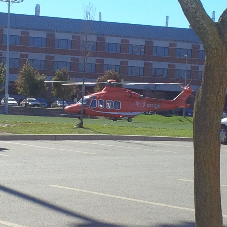 An Ornge air ambulance lands on a soccer field at Wilfrid Laurier University in Waterloo, Ont., on Friday, Oct. 11, 2013. (Courtesy @CashFlowIsKey / Twitter)