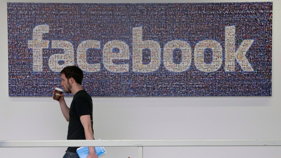 A Facebook employee walks past a sign at Facebook headquarters in Menlo Park, Calif., March 15, 2013. (AP / Jeff Chiu)