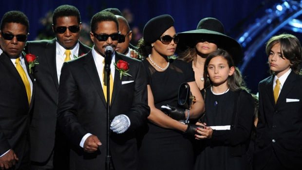 Michael Jackson's siblings, from left, Tito Jackson, Jermaine Jackson, Marlon Jackson, Randy Jackson, partially obscured, Janet Jackson, LaToya Jackson and children Paris and Prince Michael Jackson stand on the stage at the memorial service for music legend Michael Jackson at the Staples Center in Los Angeles on Tuesday, July 7, 2009. (AP Photo/Gabriel Bouys, pool)