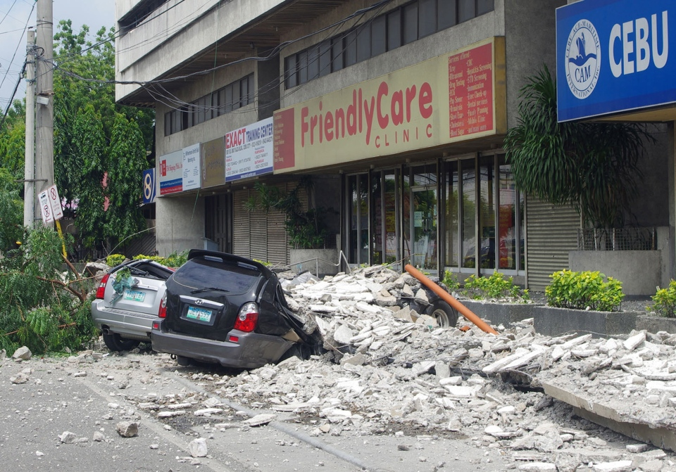 Damaged cars lie under a rubble outside the GMC Plaza Building in Cebu, central Philippines Tuesday, Oct. 15, 2013. (AP Photo/Chester Baldicantos)