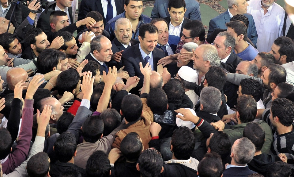 In this photo released by the Syrian official news agency SANA, Syrian President Bashar Assad, center, greets his supporters after he attended prayers on the first day of Eid al-Adha, at the Sayeda Hassiba mosque, in Damascus, Syria, Tuesday, Oct. 15, 2013. (AP / SANA)