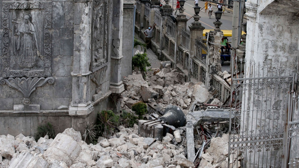 The bell of Basilica of the Holy Child lies amidst the rubble following a 7.2-magnitude earthquake that hit Cebu city in central Philippines and toppled the bell tower of the Philippines' oldest church Tuesday, Oct. 15, 2013. (AP / Bullit Marquez)