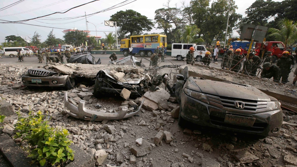 Soldiers remove the debris that fell over cars following a 7.2-magnitude earthquake that hit Cebu city in central Philippines Tuesday, Oct. 15, 2013. (AP / Bullit Marquez)