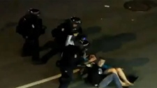 "A new video posted on the website YouTube shows ""kissing couple"" Alexandra Thomas and Scott Jones being charged by a fast-moving line of riot police before falling to the ground. (YouTube)"