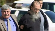 An RCMP officer escorts 62-year-old Romeo Jacques Cormier from court in Moncton, N.B.