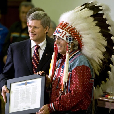 Assembly of First Nations Chief Phil Fontaine is presented with a citation by Prime Minister Stephen Harper after an official apology by the government for residential school abuse in the House of Commons in Ottawa on Wednesday, June 11, 2008. (Fred Chartrand / THE CANADIAN PRESS)