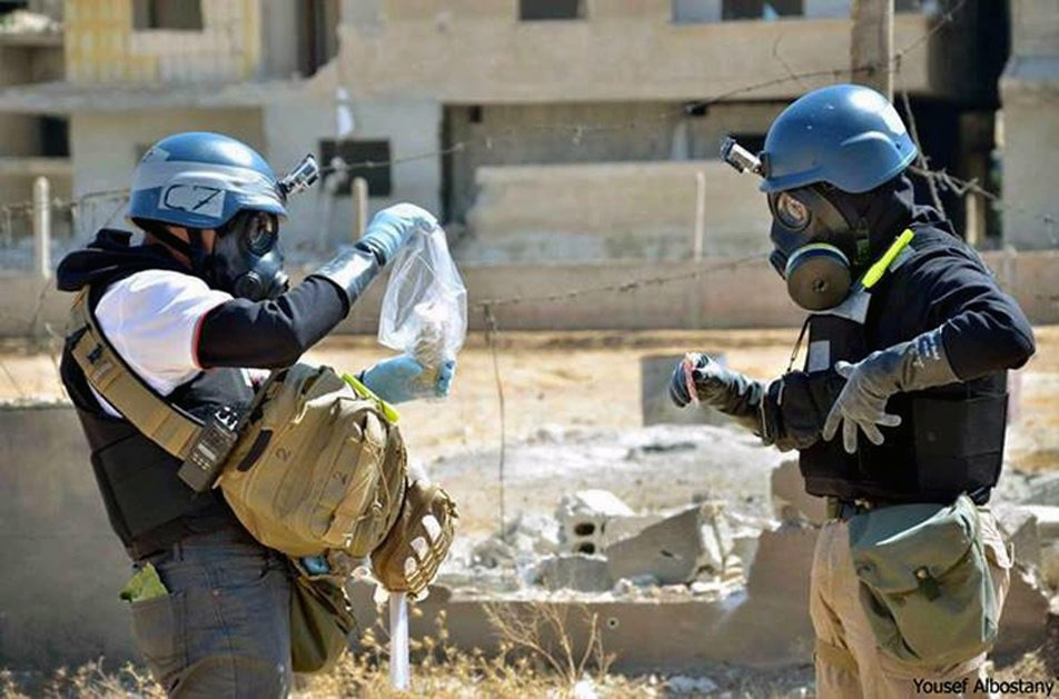 Members of the UN investigation team take samples from sand near a part of a missile that is likely to be one of the chemical rockets according to activists, in the Damascus countryside of Ain Terma, Syria, Wednesday, Aug. 28, 2013. (AP / Local Committee of Arbeen)