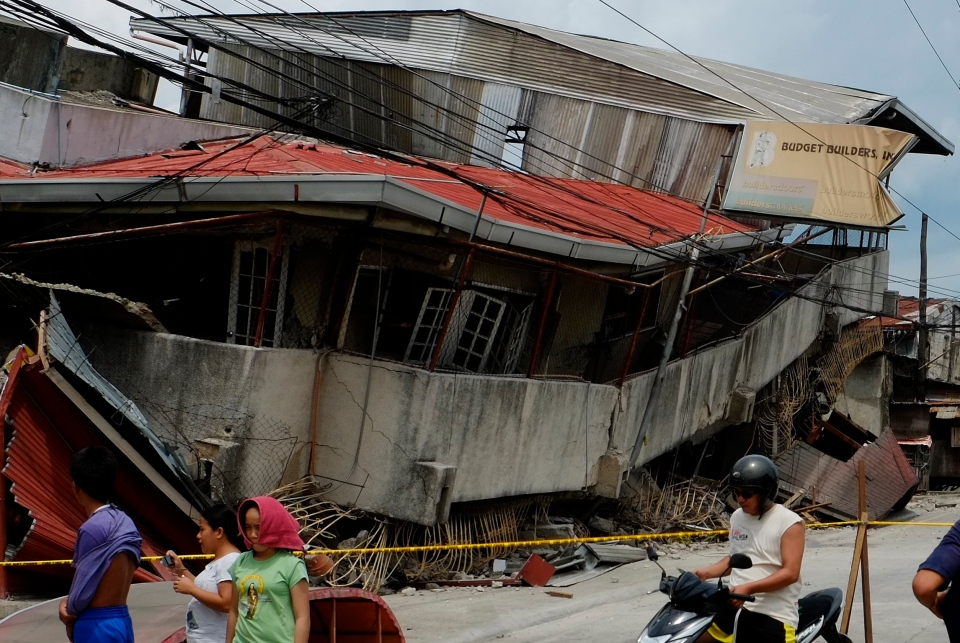 Residents walk past a damaged structure in Cebu, central Philippines on Tuesday, Oct. 15, 2013. (AP / Erwin Lim)