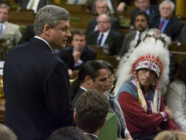 Asembly of First Nations Chief Phil Fontaine (right, wearing headdress) watches as Prime Minister Stephen Harper officially apologizes for more than a century of abuse and cultural loss involving Indian residential schools at a ceremony in the House of Commons on Parliament Hill in Ottawa, Wednesday, June 11, 2008. (Tom Hanson / THE CANADIAN PRESS)