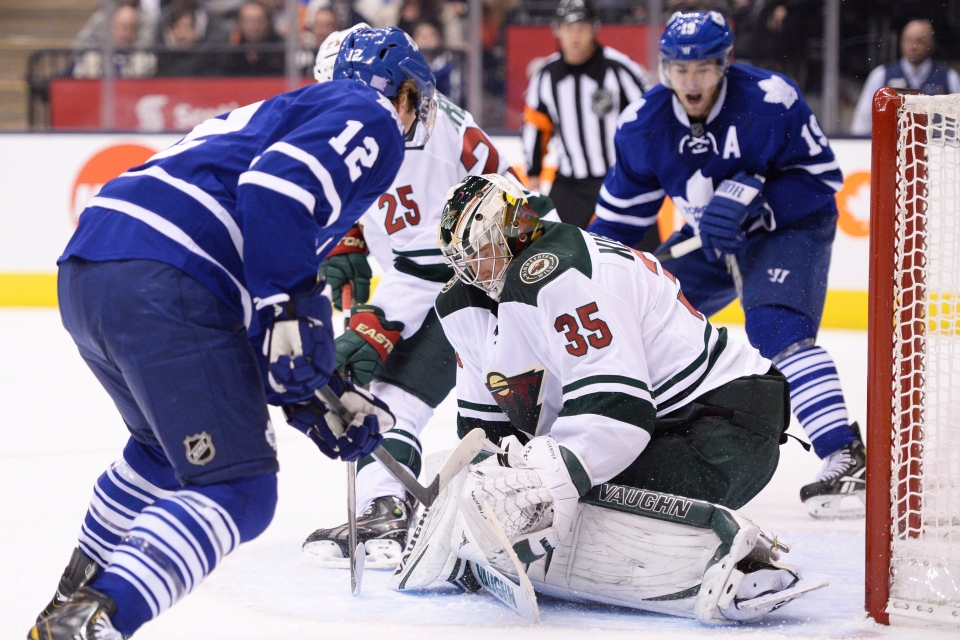 Minnesota Wild goalie Darcy Kuemper searches for the puck as Toronto Maple Leafs' Mason Raymond (12) and Joffrey Lupul (19) look on during second period NHL action in Toronto on Tuesday, October 15, 2013. (Frank Gunn/ THE CANADIAN PRESS)