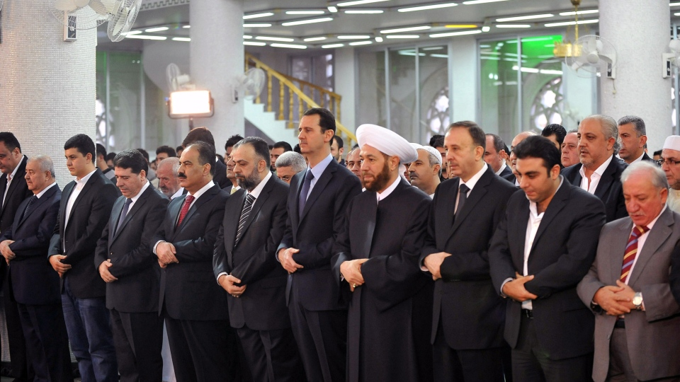 In this photo released by the Syrian official news agency SANA, Syrian President Bashar Assad, fifth from right, prays during the Eid al-Adha prayer at the Sayeda Hassiba mosque, in Damascus, Syria, Tuesday, Oct. 15, 2013. (AP / SANA)