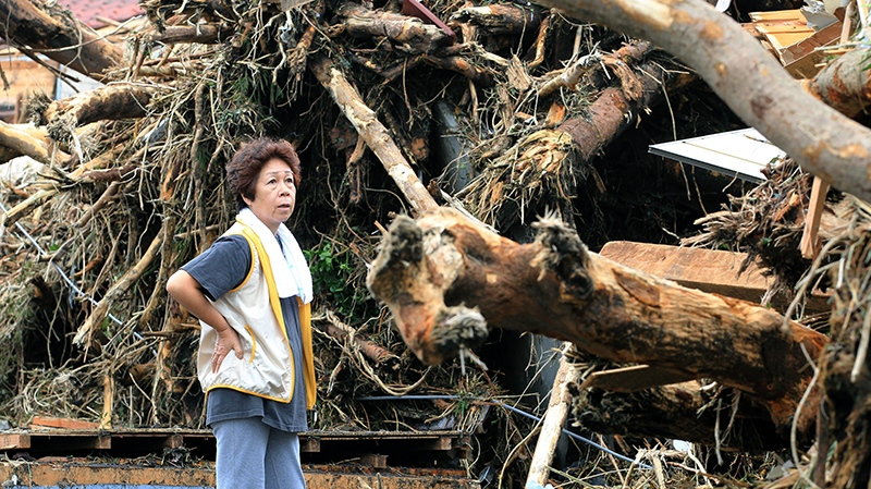 A woman looks at the aftermath of landslides in the rubble of smashed houses in Oshima after a powerful typhoon hit Izu Oshima island, about 120 kilometres south of Tokyo Wednesday morning, Oct. 16, 2013. (AP Photo/Kyodo News)