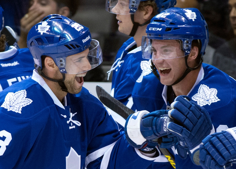Toronto Maple Leafs' Tyler Bozak (right) congratulates teammate Trevor Smith after his first goal as a Leaf against the Minnesota Wild in Toronto on Tuesday, Oct. 15, 2013. (Frank Gunn / THE CANADIAN PRESS)