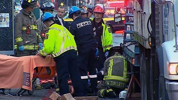 Toronto EMS workers tend to a female cyclist who was struck by a truck in downtown Toronto, Wednesday, Oct. 16, 2013.