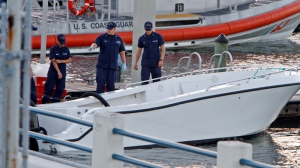 U.S Coast Guard personnel inspects a vessel with a missing center console that capsized near Miami, Wednesday Oct. 16, 2013. The Coast Guard responded to an early morning call and found nine people clinging to the hull seven miles east of Miami. Four women died and 10 other people were taken into custody after the boat with more than a dozen people aboard, including Haitian and Jamaican nationals, capsized in the waters off South Florida. Authorities are investigating whether the victims and survivors were part of a human smuggling operation. (AP / Miami Herald, Walter Michot)