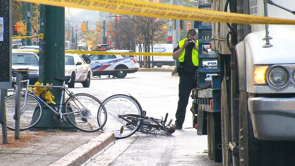 Police take photos of the scene where a female cyclist was struck by a truck in downtown Toronto, Wednesday, Oct. 16, 2013.