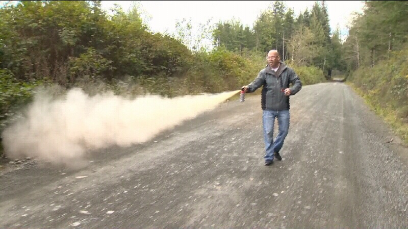 Mountie Carl McIntosh shows how he discharged bear spray when a cougar stalked him, his wife and their two dogs while they were on a walk Monday. Oct. 16, 2013. (CTV)