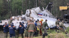 Emergency workers carry a stretcher with a body near the wreckage of a Tu-134 plane, belonging to the RusAir airline, near the city of Petrozavodsk on Tuesday, June 21, 2011.