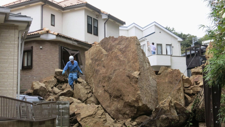 A fire fighter walks over rocks fallen from a cliff over a garage and a road in a residential area in Kamakura, southwest of Tokyo, after a powerful typhoon hit Japan's metropolitan area Wednesday morning, Oct. 16, 2013. (AP / Kyodo News)