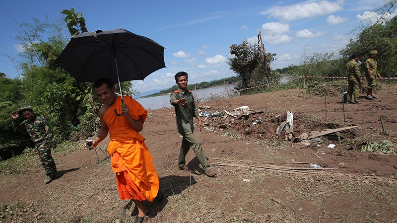 Lao soldiers ask a monk to leave from the crash site of a Laos Airlines plane in Pakse, Laos Thursday, Oct. 17, 2013. (AP / Sakchai lalit)