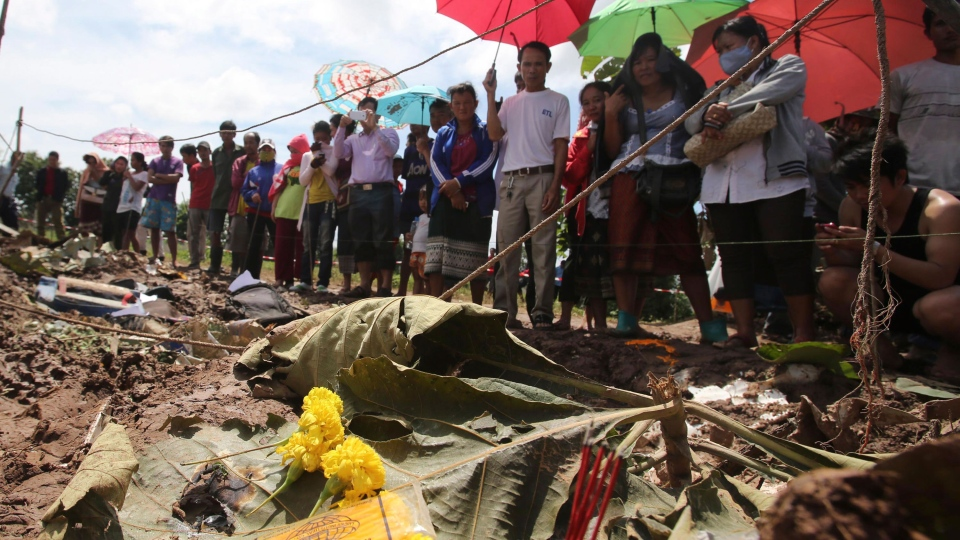 People look at the debris of a Lao Airlines turboprop plane that crashed, in Pakse, Laos on Thursday, Oct. 17, 2013. (AP / Sakchai Lalit)