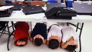 Fifth-graders take cover under a table during an earthquake drill at Hilton Head Island Elementary School on Thursday, Oct. 18, 2012. (The Island Packet / Jay Karr)