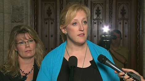 Labour Minister Lisa Raitt speaks with the media in the foyer of the House of Commons in Ottawa, Friday, June 24, 2011.