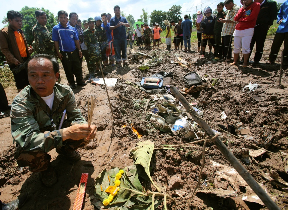 A Lao soldier prepares to place incense sticks into the ground beside the wreckage left by a Lao Airlines turboprop plane as he pays his respects to the victims of Wednesday's ill-fated flight, in Pakse in Laos, Thursday, Oct. 17, 2013. (AP / Sakchai Lalit)