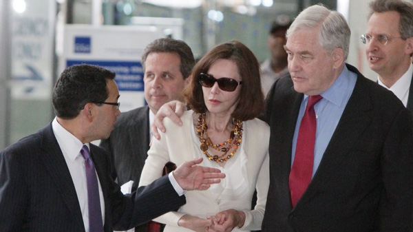 Former media mogul Conrad Black and his wife Barbara Amiel Black listen to attorney Miguel Estrada as they leave Federal court in Chicago on Friday, June 24, 2011. (AP /M. Spencer Green)