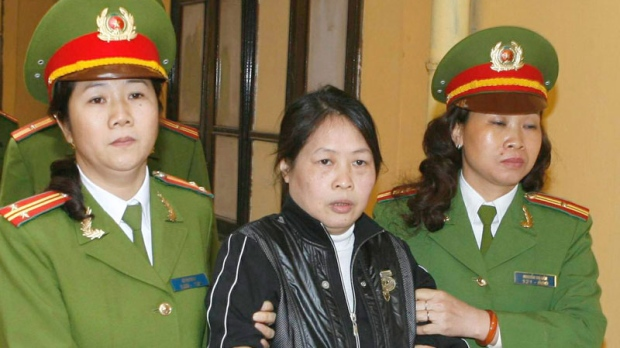 Dissident writer Tran Khai Thanh Thuy is escorted from a court room in Hanoi, Vietnam Friday, April 16, 2010.
