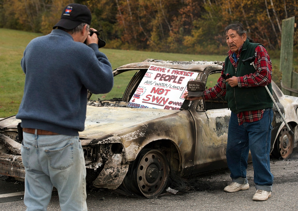 Protesters take photos of a burned out police vehicle in Rexton, N.B. on Thursday, Oct. 17, 2013. (Andrew Vaughan / THE CANADIAN PRESS)